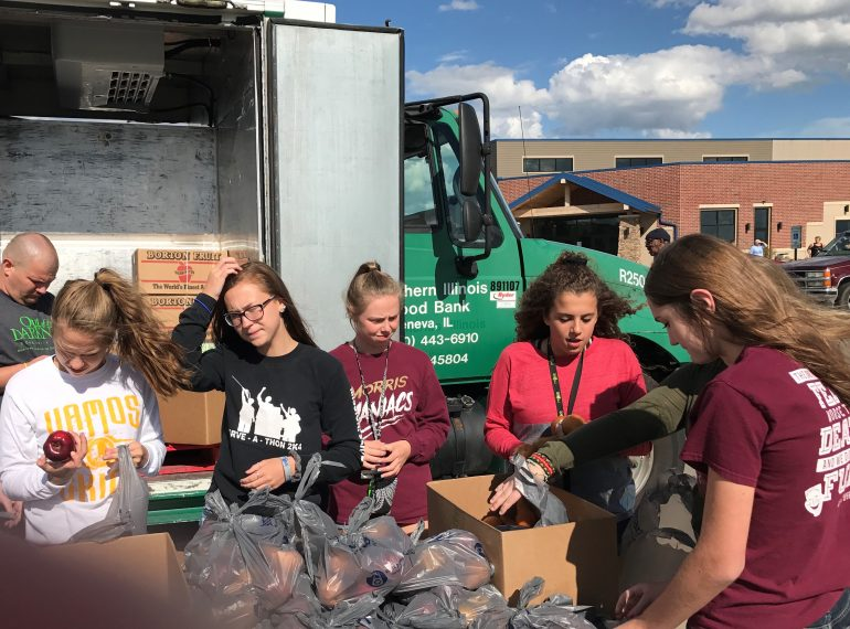 High school students volunteer at The Village Christian Church food truck in MInooka., Il to serve families struggling in the community.
